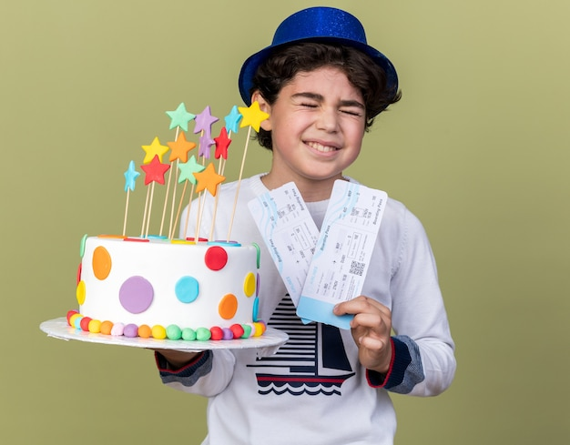 Joyful with closed eyes little boy wearing blue party hat holding tickets with cake isolated on olive green wall