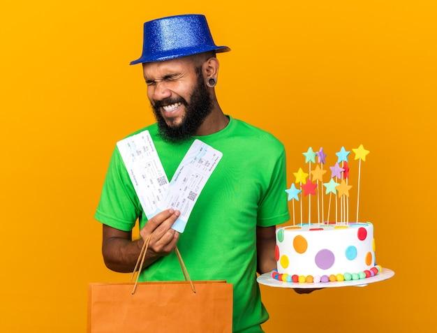 Gioioso con gli occhi chiusi giovane ragazzo afroamericano che indossa un cappello da festa con una borsa regalo e una torta con i biglietti
