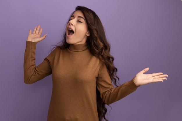 닫힌 된 눈으로 즐거운 젊은 아름 다운 소녀 보라색 벽에 고립 된 손을 확산 갈색 터틀넥 스웨터를 입고