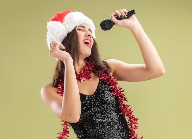 Радостная с закрытыми глазами молодая красивая девушка в новогодней шапке с гирляндой на шее держит микрофон и поет на оливково-зеленом фоне