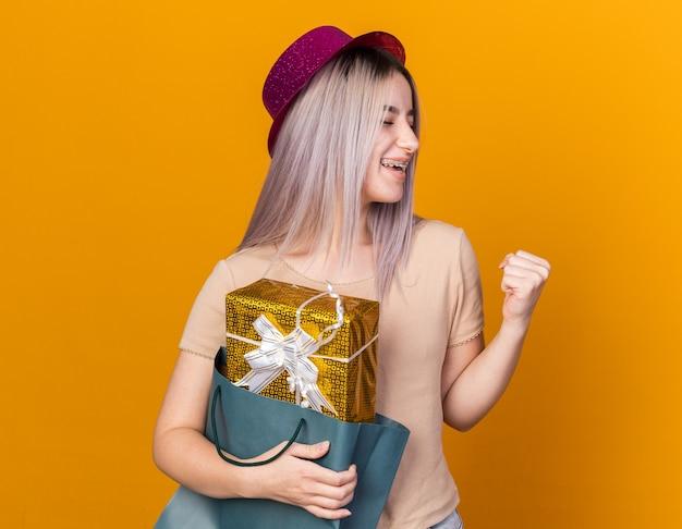 Радостная с закрытыми глазами молодая красивая девушка в партийной шляпе с подтяжками, держащая подарочный пакет, показывая жест да, изолированный на оранжевой стене