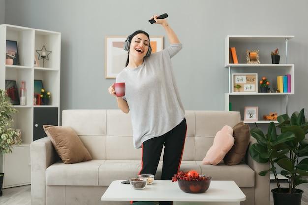 Gioiosa con gli occhi chiusi ragazza che indossa le cuffie che tiene il telecomando della tv con una tazza di tè in piedi dietro il tavolino da caffè in soggiorno