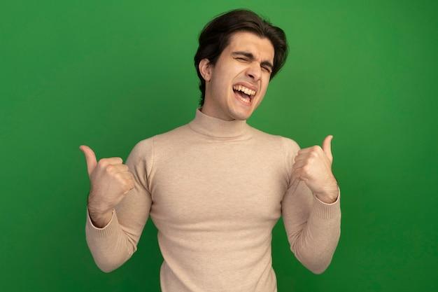 닫힌 된 눈으로 즐거운 젊은 잘 생긴 남자 엄지 손가락을 보여주는 녹색 벽에 고립