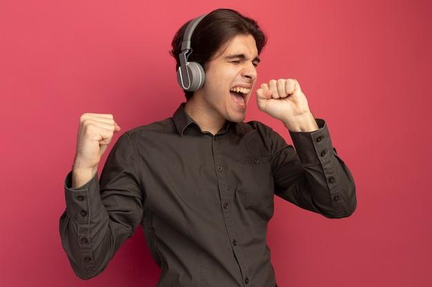 닫힌 된 눈으로 즐거운 젊은 잘 생긴 남자 헤드폰으로 검은 색 티셔츠를 입고 분홍색 벽에 고립 된 노래