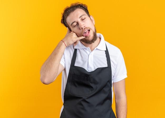 노란색 벽에 고립 된 혀와 전화 제스처를 보여주는 제복을 입고 닫힌 된 눈 젊은 남성 이발사와 즐거운