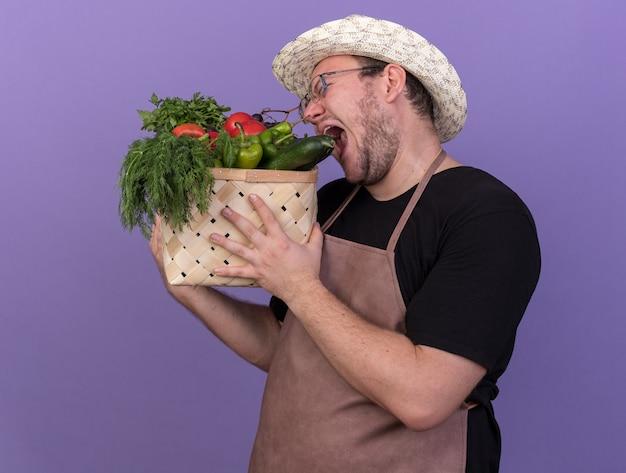 Gioioso con gli occhi chiusi giovane giardiniere maschio che indossa un cappello da giardinaggio che tiene cesto di verdure e morde il cetriolo isolato sulla parete blu
