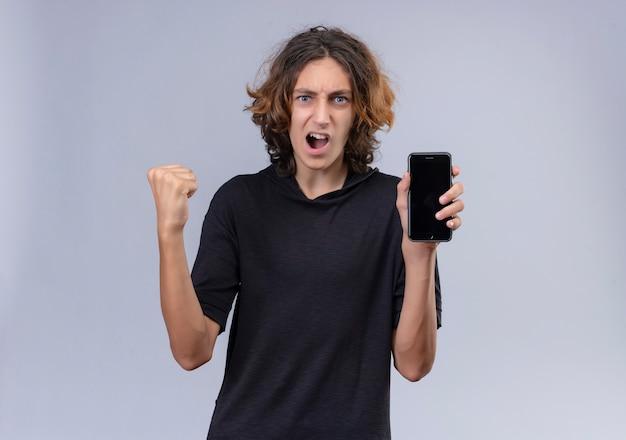 흰 벽에 전화를 들고 검은 티셔츠에 긴 머리를 가진 감정 남자와 즐거운