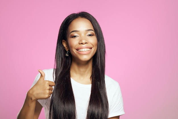 Joyful woman of african appearance in white tshirt long hair pink background