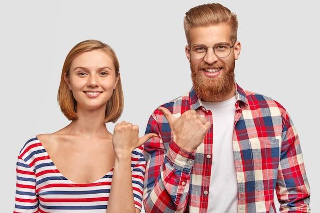 うれしそうな女性と男性の親友はお互いに示し、顔に優しい笑顔を持ち、注目を集める