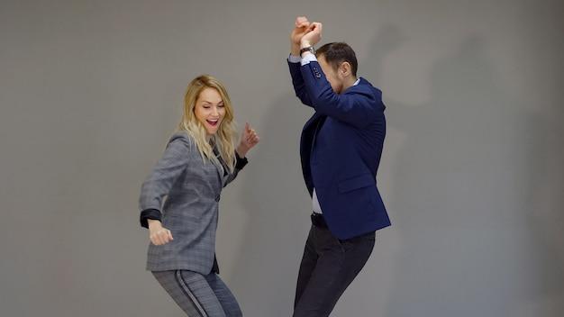 Радостная женщина и мужчина в деловых костюмах танцуют на сером фоне.