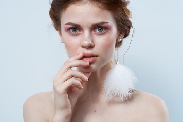 Joyful woman bare shoulders fluffy earrings cosmetics glamor