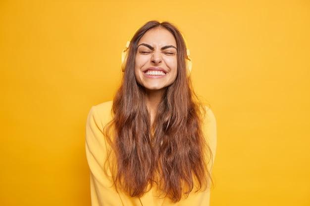 うれしそうな女性は目を閉じ、ニヤリと笑いながらヘッドフォンで音楽を聴き、黄色い壁の上にカジュアルな服装をした長い黒髪をしている。人々の趣味のレジャーとエンターテイメントのコンセプト。