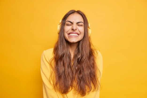 Joyful woman closes eyes and grins  listens music via headphones has long dark hair dressed casually isolated over yellow wall. people hobby leisure and entertainment concept.