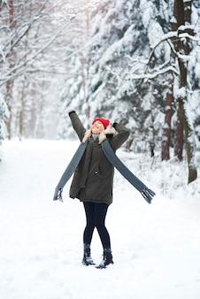 Donna allegra che balla nella foresta di inverno