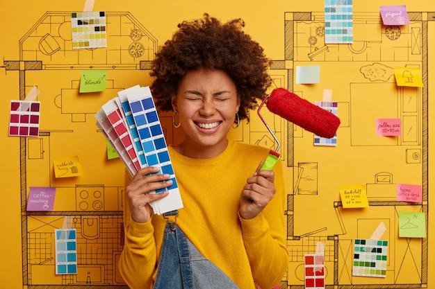 Designer donna gioiosa tiene il rullo di vernice e la tavolozza dei colori, sceglie il tono appropriato per la ristrutturazione, ha buon umore