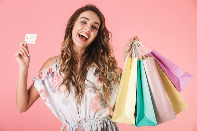 Joyful woman in dress holding credit card and colorful shopping bags, isolated on pink