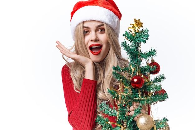 サンタのクリスマスツリーのホリデーギフトのライフスタイルに扮した楽しい女性。高品質の写真