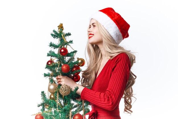 サンタのクリスマスツリーのホリデーギフトのライフスタイルに扮したうれしそうな女性