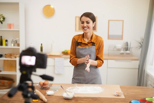 Joyful woman filming baking video in kitchen