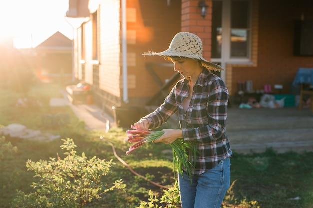 うれしそうな女性の庭師は、晴れた暖かい春の日にネギの束を保持します。植物の世話と収穫の概念と趣味