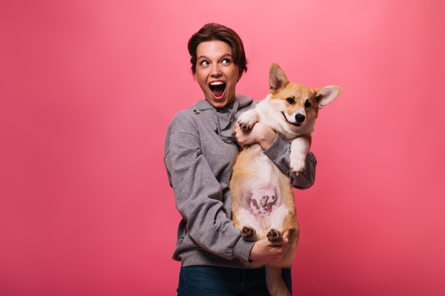 Donna allegra in felpa con cappuccio grigia che tiene corgi su sfondo rosa. ragazza teenager emotiva in jeans gioca con il cane su isolato