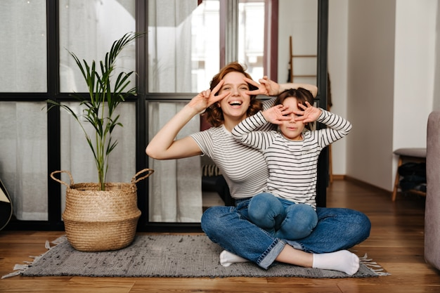Joyful woman and her daughter having fun in living room and showing signs of peace.