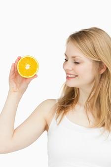 Joyful woman holding an orange