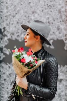 Donna allegra che tiene un mazzo di fiori