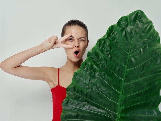 Joyful woman holding hands near face palm leaf swimsuit light background
