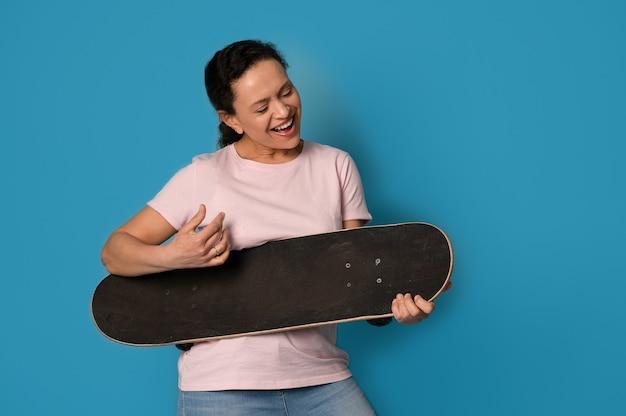 Радостная женщина, держащая скейтборд как гитару на синем фоне