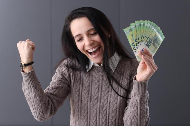 うれしそうな女性は彼女の手にユーロを持っています。在宅勤務とギャンブルの概念