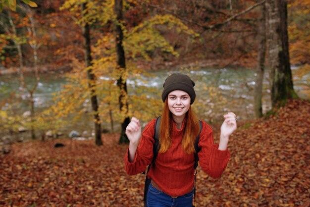 自然の公園で彼女の手で彼女の背中のジェスチャーにバックパックと帽子のセーターを着たうれしそうな女性