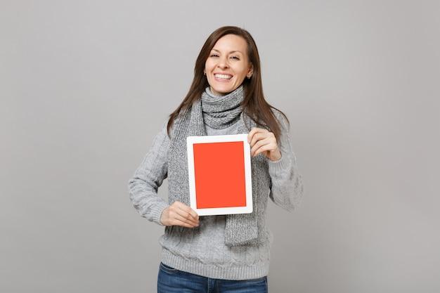 灰色のセーター、スカーフは灰色の背景に分離された空白の空の画面でタブレットpcコンピューターを保持します。健康的なライフスタイル、寒い季節のコンセプトをコンサルティングするオンライン治療。コピースペースをモックアップします。