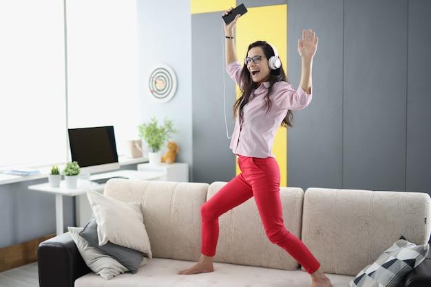 Радостная женщина в наушниках со смартфоном танцует на диване