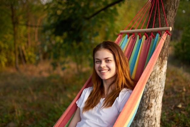自然の中でうれしそうな女性はハンモック休憩の快適さにあります