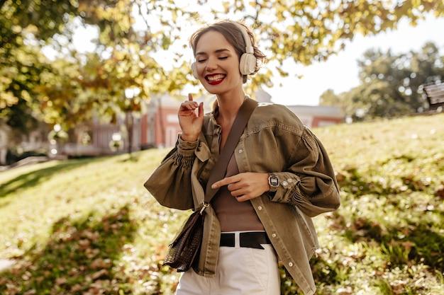 올리브 재킷과 흰색 청바지 밖에 서 웃 고있는 즐거운 여자. 야외에서 음악을 듣고 핸드백과 헤드폰에 물결 모양의 머리 여자.
