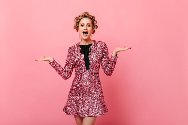 ピンクのドレスを着たうれしそうな女性が孤立した壁で笑う