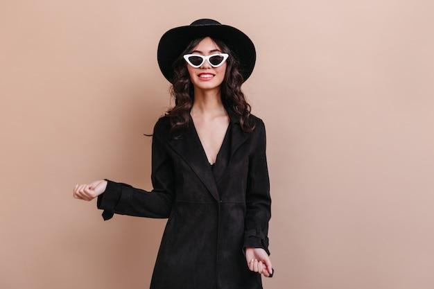 カメラを見てサングラスと帽子のうれしそうな女性。黒のコートを着た女性モデルの正面図。