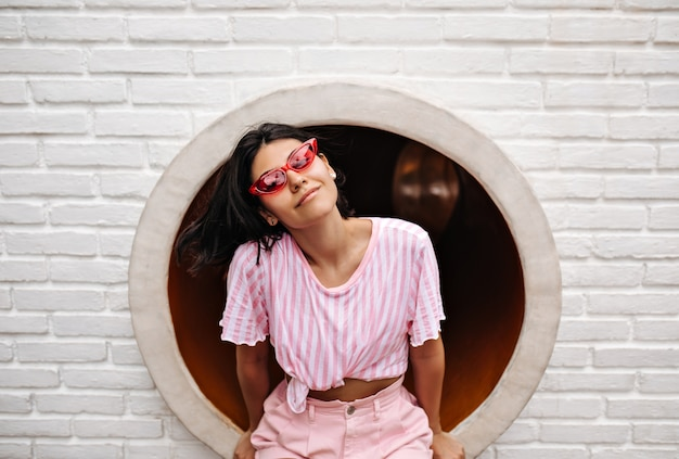 レンガの壁に座っているtシャツのうれしそうな女性。トレンディなサングラスをかけた魅力的な女性の屋外ショット。