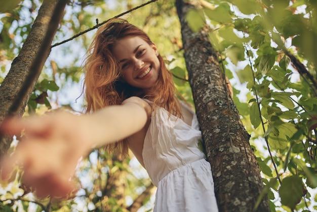 木の自然の夏の近くの白いドレスを着たうれしそうな女性。高品質の写真