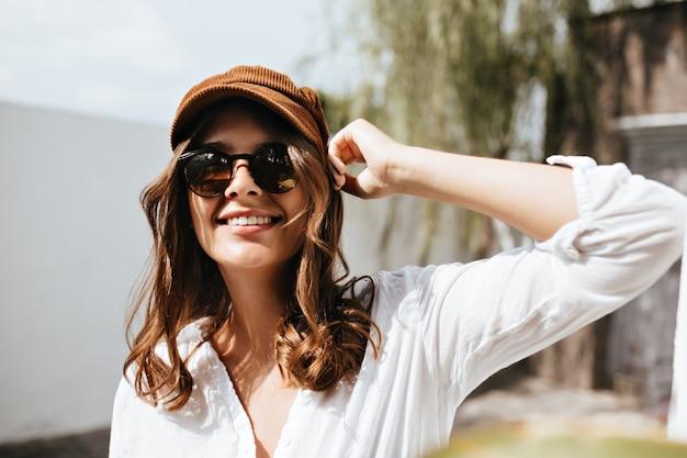 カメラを見て笑顔で白くて軽いvネックブラウスのうれしそうな女性。建物や木のスペースに対してポーズをとってキャップとメガネの女の子。