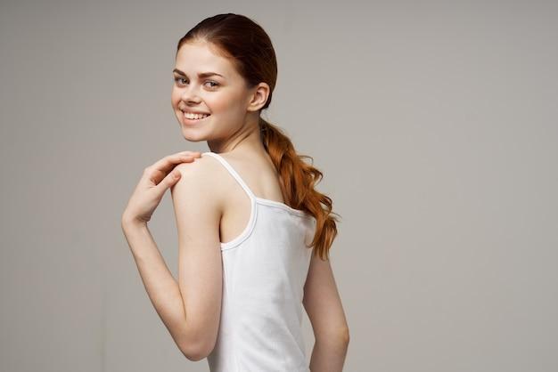 Радостная женщина в суставах белой футболки разогревается