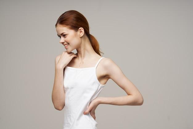 白いtシャツの関節のうれしそうな女性がウォームアップ