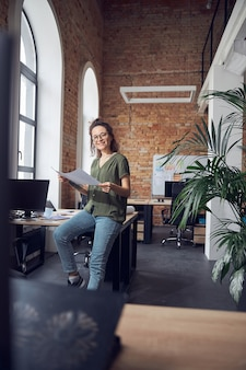 Joyful woman interior designer or architect wearing glasses smiling at camera while working