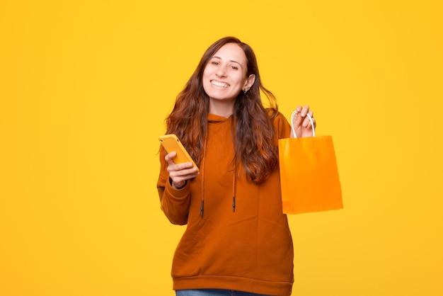 Радостная женщина улыбается и держит сумку для покупок и телефон