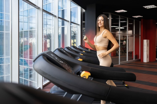 Joyful woman jogging in the gym