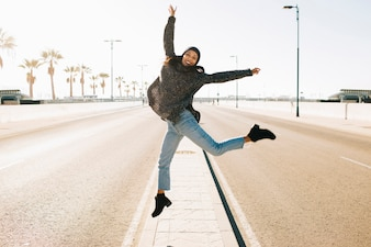 Joyful woman jumping in middle of the street