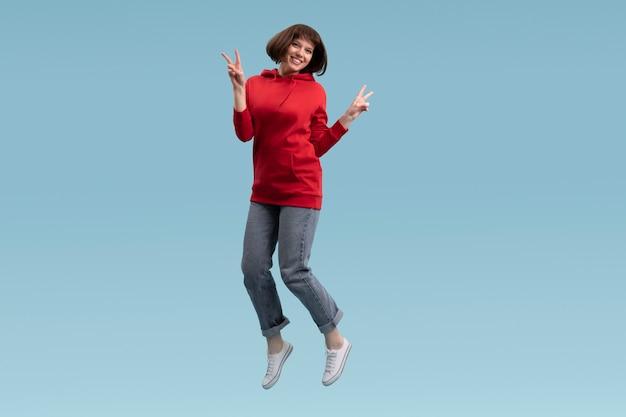 Donna allegra che salta isolato sull'azzurro