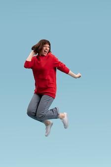 Joyful woman jumping isolated on blue