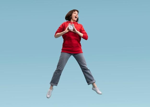 青に孤立してジャンプするうれしそうな女性